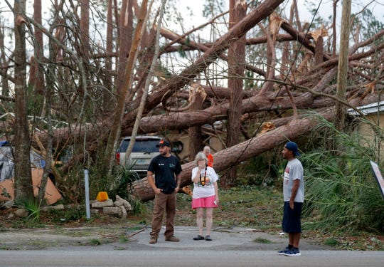 Joyce Fox, center stands in front of her heavily damaged home in the aftermath of Hurricane Michael in Panama City, Fla., Thursday, Oct. 11, 2018. (AP Photo/Gerald Herbert)