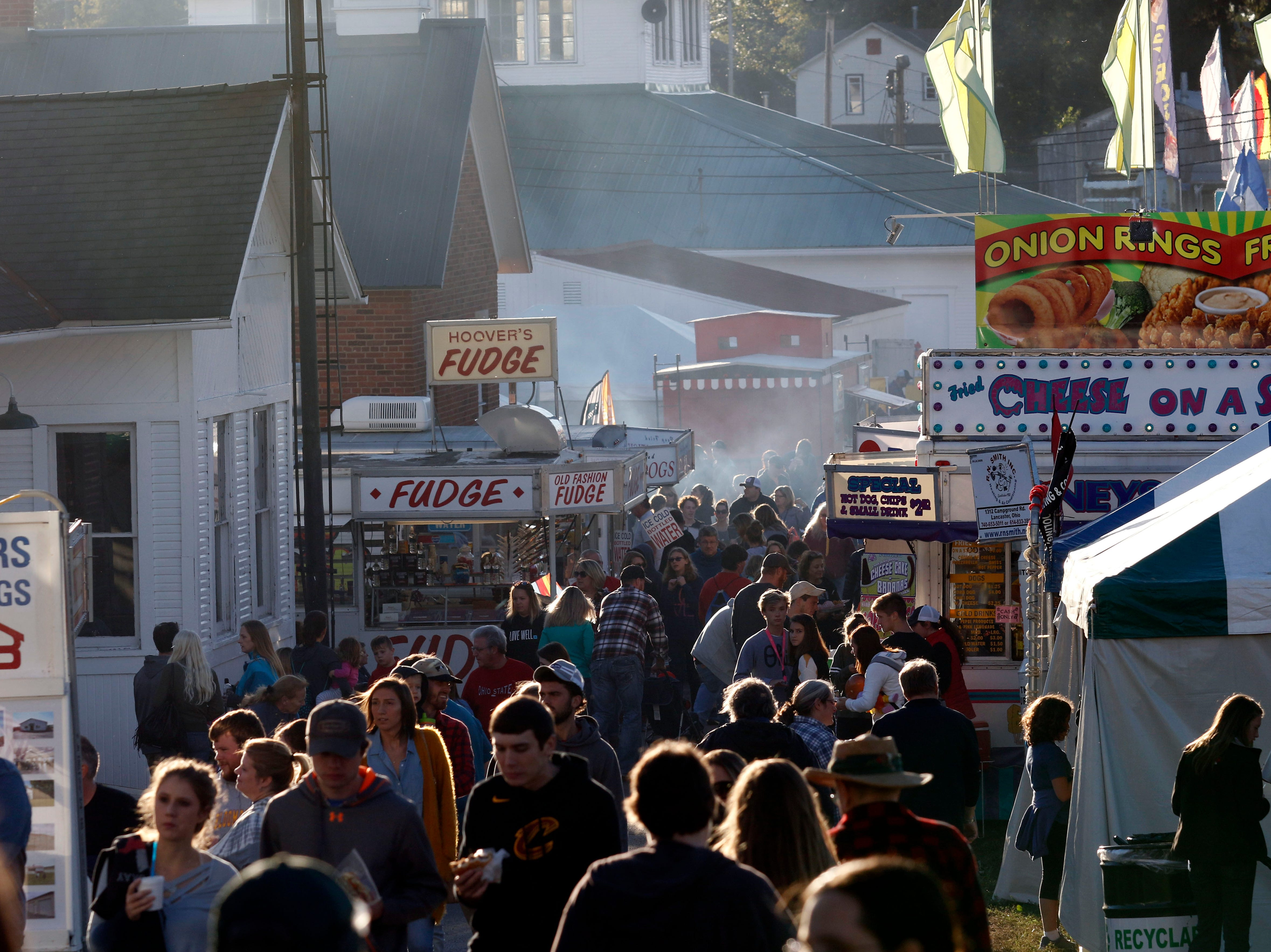 People walk amongst a small selection of food vendors Thursday evening, Oct. 11, 2018, at the Fairfield County Fair in Lancaster.