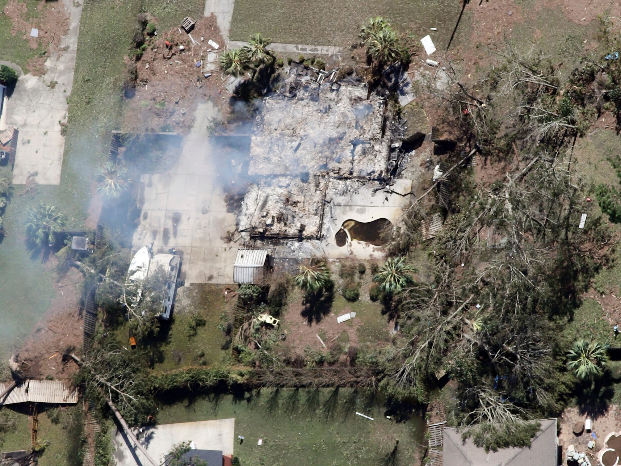 This aerial photo shows a home smoldering, Thursday, Oct. 11, 2018, in Mexico Beach, Fla. The devastation inflicted by Hurricane Michael came into focus Thursday with rows upon rows of homes found smashed to pieces, and rescue crews began making their way into the stricken areas in hopes of accounting for hundreds of people who may have stayed behind. (Michael Snyder/Northwest Florida Daily News via AP)