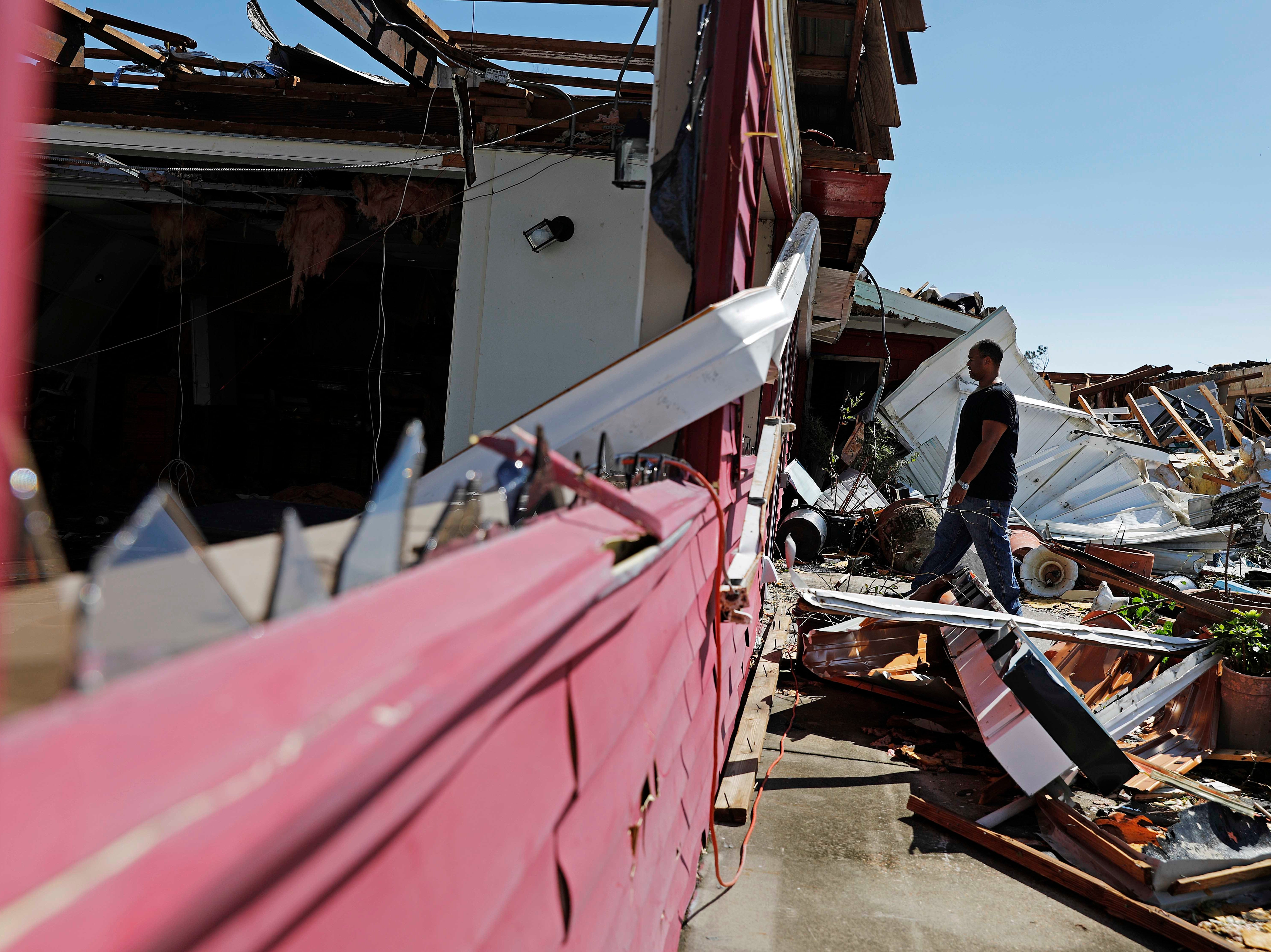 Matthew Washington walks in to salvage items from the damaged Thai restaurant he owns with his wife in the aftermath of hurricane Michael in Callaway, Fla., Thursday, Oct. 11, 2018. (AP Photo/David Goldman)