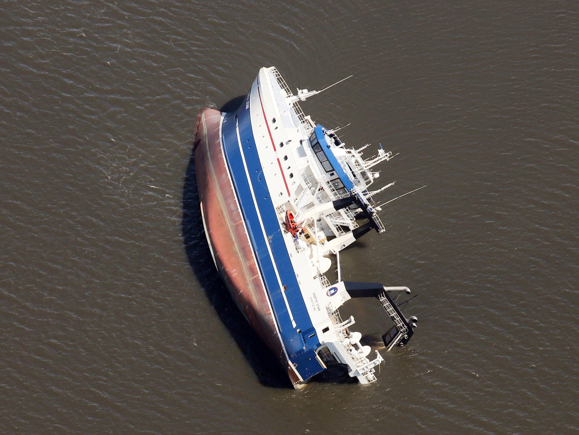 A large ship lists on its side in the St. Andrew Bay, at Panama City, Fla., Thursday, Oct. 11, 2018. The devastation inflicted by Hurricane Michael came into focus Thursday with rows upon rows of homes found smashed to pieces, and rescue crews began making their way into the stricken areas in hopes of accounting for hundreds of people who may have stayed behind. (Michael Snyder