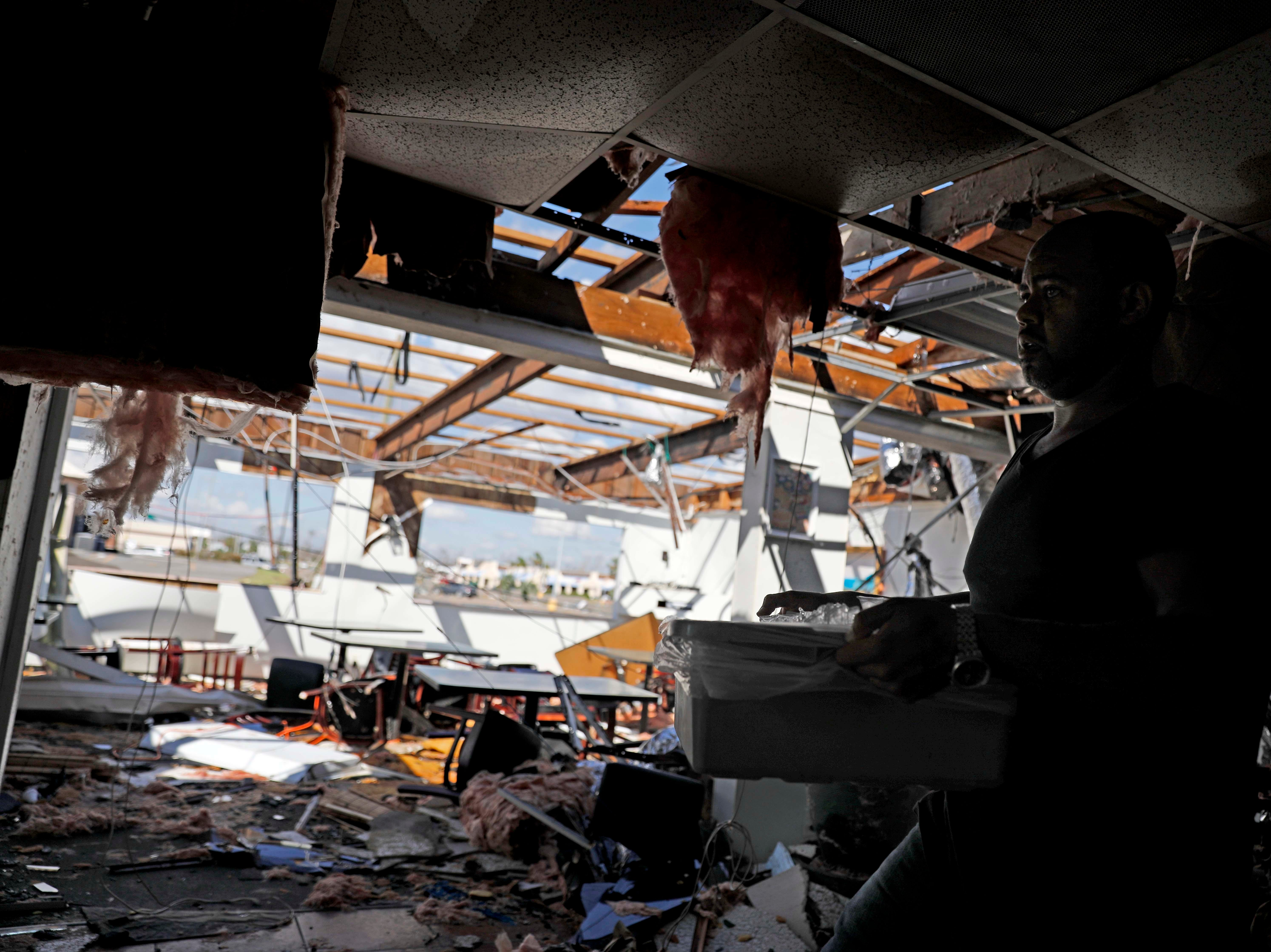 Matthew Washington carries out ice while retrieving salvageable items from the damaged Thai restaurant he owns with his wife in the aftermath of hurricane Michael in Callaway, Fla., Thursday, Oct. 11, 2018. (AP Photo/David Goldman)