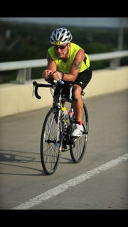 Randall Bowden rides a bike during a triathlon.