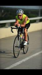 Randall Bowden rides a bike during a triathlon.