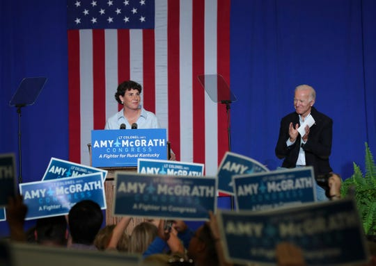 Congressional candidate Amy McGrath, left, was applauded by the crowd and former Vice President Joe Biden during her campaign speech at the Bath County High School. Oct. 12, 2018