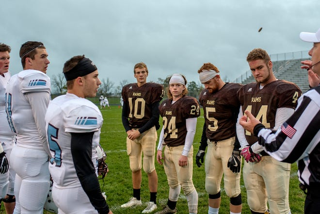 The Holt and Okemos captains watch the coin flip before the game on Friday, Oct. 12, 2018, at Holt High School. Okemos won the flip and opted to receive.