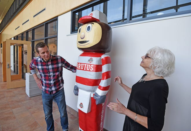 Artist Ryan Failor and the co-creator of Brutus Buckeye, Sally Lanyon, admire the mascot statue on display in Riedl Hall on Friday.