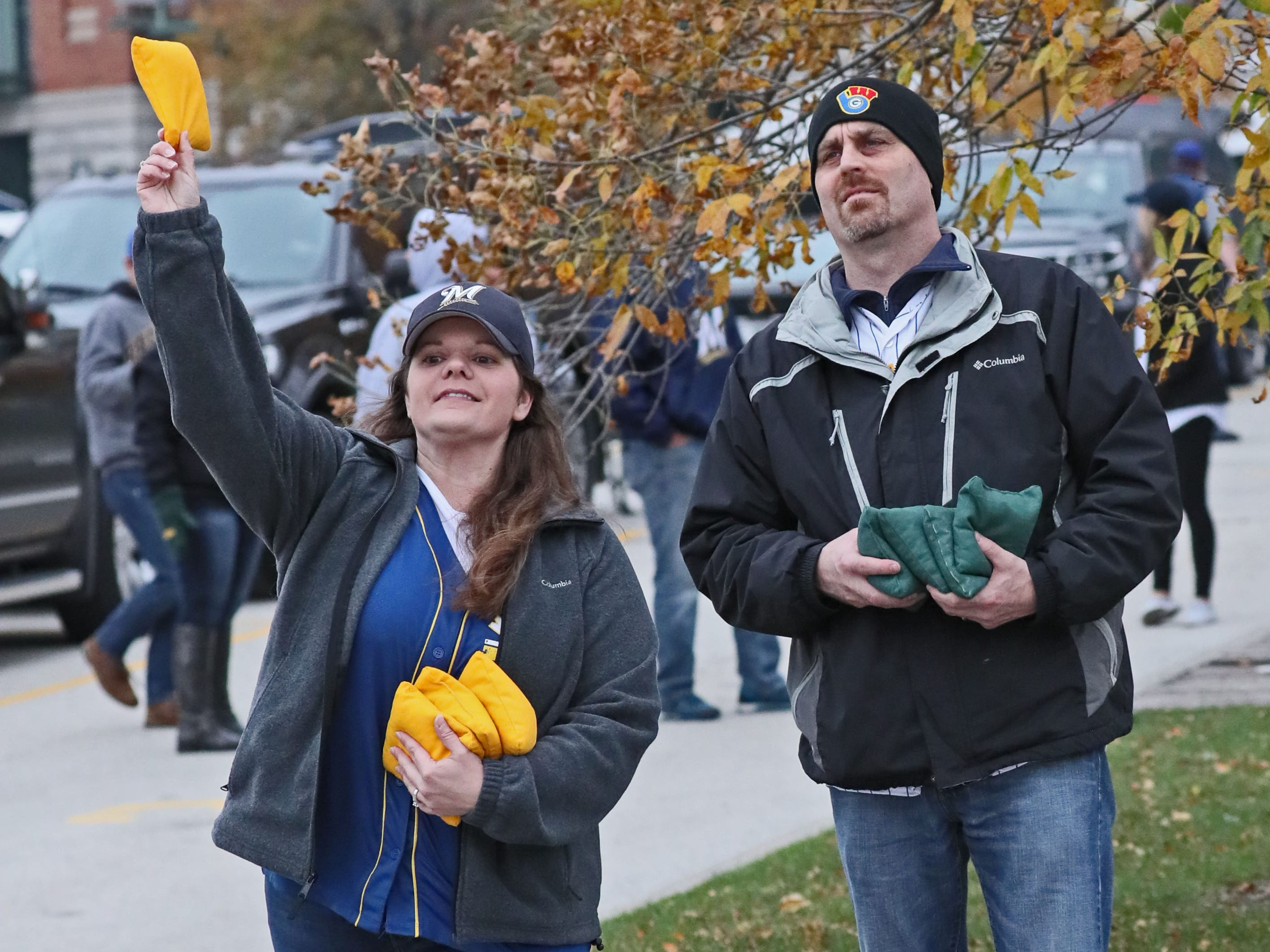 Stephanie Baumeister (left) and her husband, Andrew Baumeister of Pewaukee, played a game of bean bag toss as they tailgated before the game.