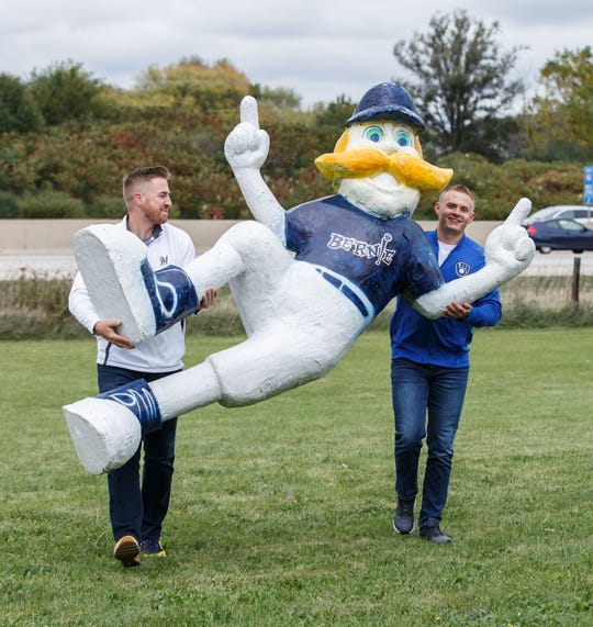 Clear Channel Outdoor employees Eric Hamme (left) and Max O'Neil bring a statue of Bernie Brewer back into their building in Pewaukee on Friday afternoon, Oct. 12. The company temporarily placed the statue along I-94 to welcome Milwaukee Brewers fans headed to Friday's game.