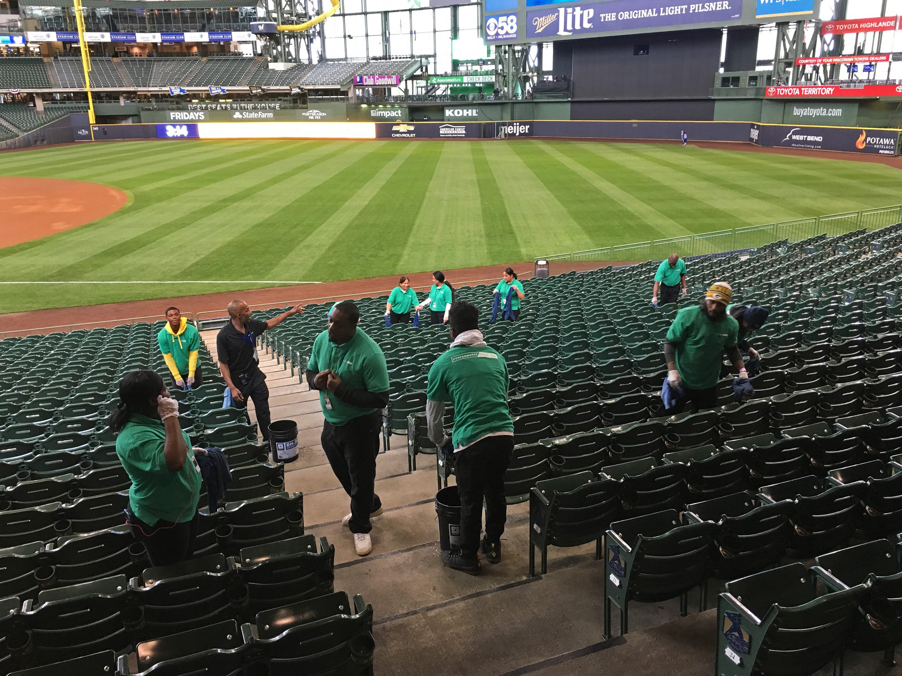 Stadium staff clean the seats before the fans arrive for NLCS Game 1 at Miller Park.