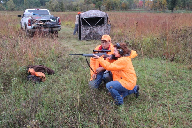 John Motoviloff assists Ellen Rice during a firearm handling session of a Learn To Hunt program of the Aldo Leopold Foundation near Baraboo.