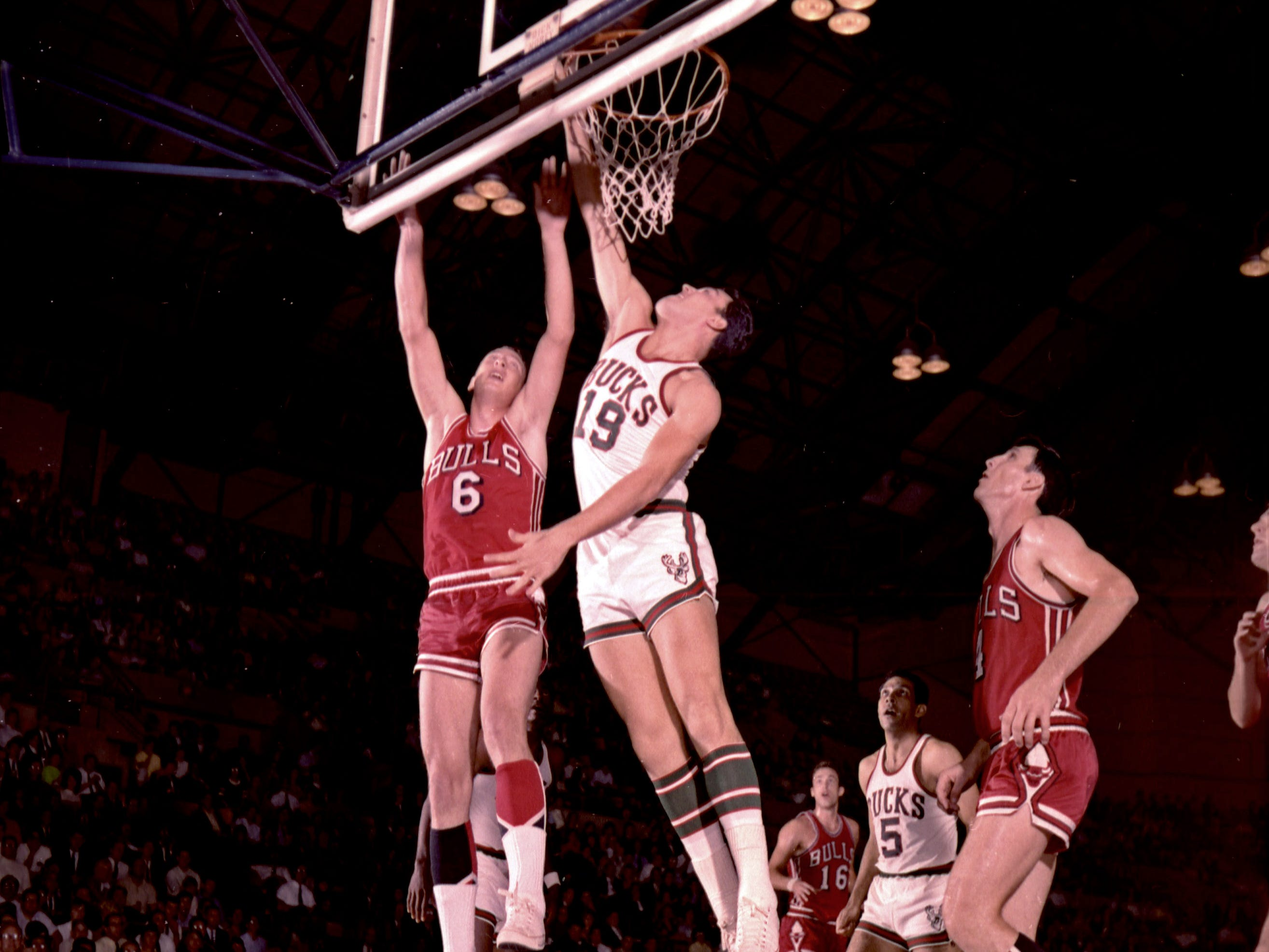Milwaukee Bucks center Dick Cunningham (19) blocks a shot by Chicago Bulls forwrad Erwin Mueller (6) in the Bucks' inaugural regular-season NBA game on Oct. 16, 1968, at the Milwaukee Arena. Bulls guard Jerry Sloan (4) looks on. The Bucks lost, 89-84.