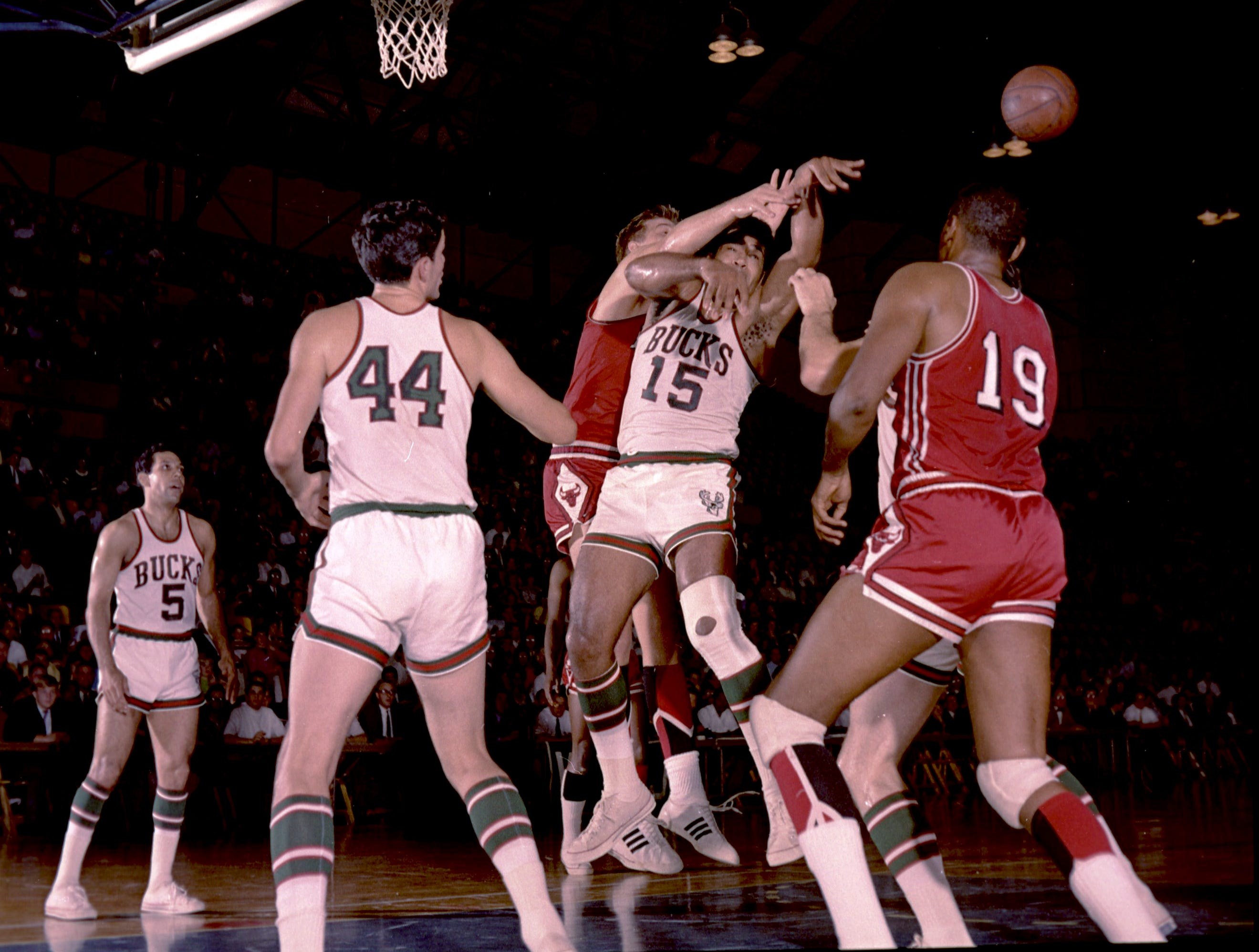Bucks center Wayne Embry (15) tussles under the basket for the ball during Milwaukee's first regular-season game in the NBA on Oct. 16, 1968, against the Chicago Bulls at the Milwaukee Arena. Looking on are Bucks guards Guy Rodgers (5) and Jon McGlocklin (14), and Bulls forward Bob Boozer (19). The Bucks lost, 89-84.