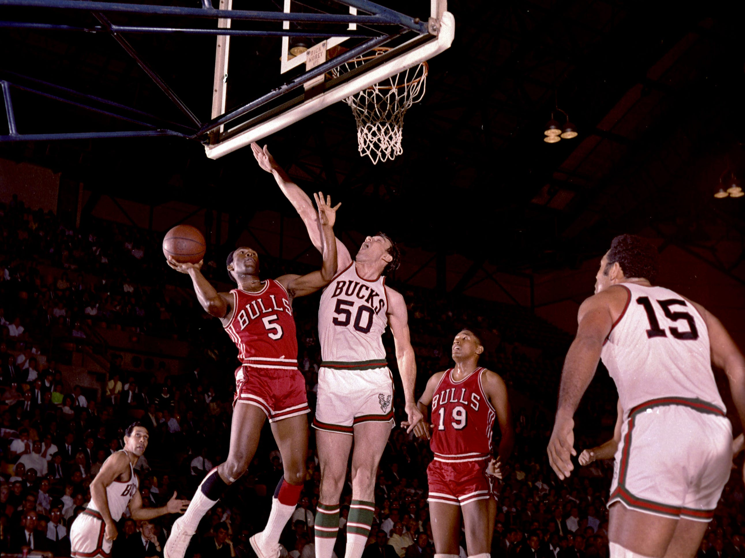 Chicago Bulls guard Flynn Robinson (5) tries to shoot over Milwaukee Bucks forward Len Chappell (50) during the Bucks' first regular-season game in the NBA on Oct. 16, 1968, at the Milwaukee Arena. Players looking on include Bucks center Wayne Embry (15, right) and Bulls forward Bob Boozer. The Bucks lost, 89-84.