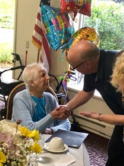 Mayor Ken Tutaj shakes the hand of Anne Psenko during her 100th birthday celebration at Howard Village in St. Francis.
