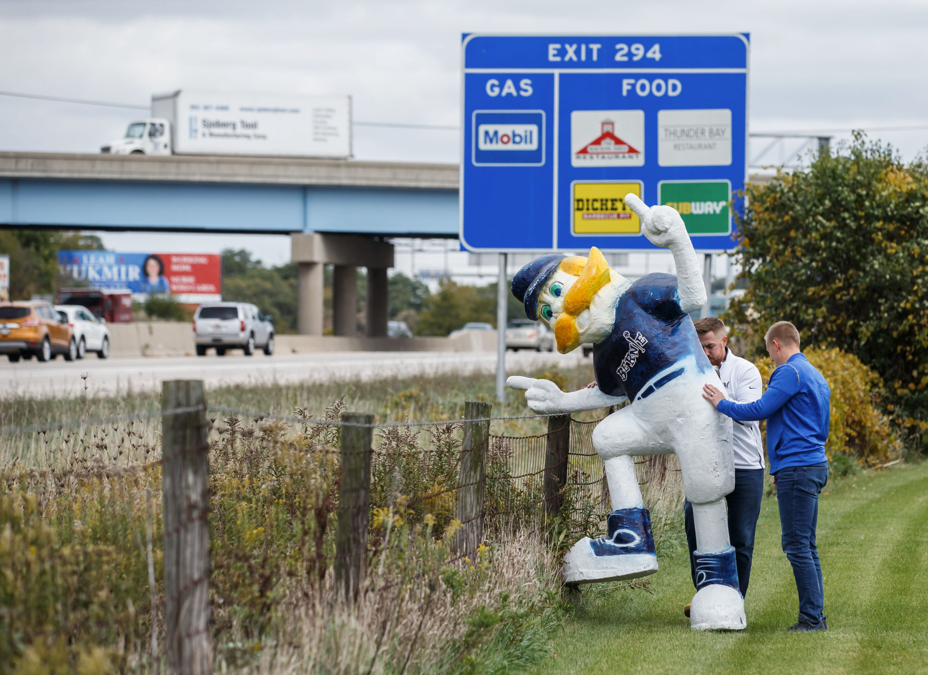 Clear Channel Outdoor employees Eric Hamme (left) and Max O'Neil prepare to bring a statue of Bernie Brewer back into their building in Pewaukee on Friday afternoon, Oct. 12. The company temporarily placed the statue along I-94 to welcome Milwaukee Brewers fans headed to Friday's game.