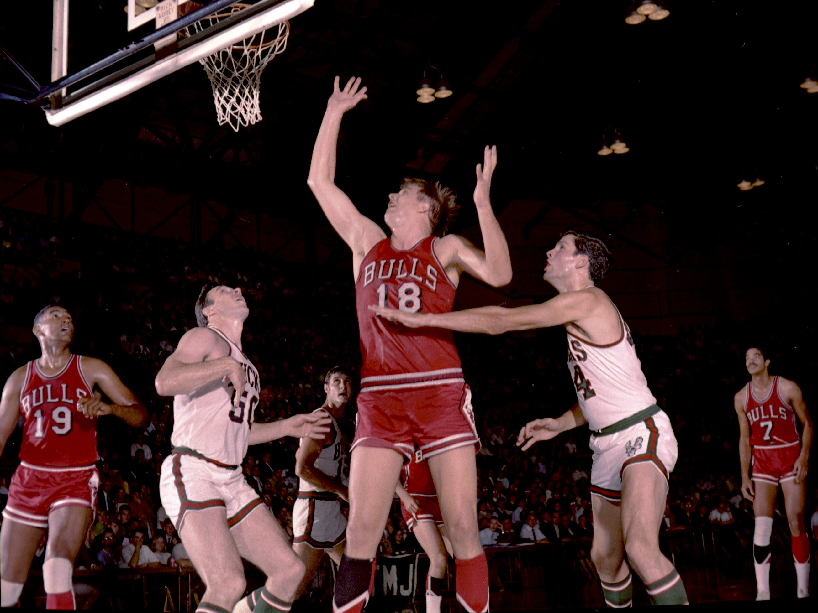 Chicago Bulls center Tom Boerwinkle (18) tosses in a shot against Milwaukee in the Bucks' first game as an NBA franchise on Oct. 16, 1968, at the Milwaukee Arena. Also under the basket are the Bulls' Bob Boozer (19), the Bucks' Len Chappell (50) and Fred Hetzel (44). The Bucks lost, 89-84.