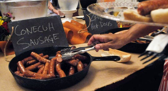 Conecuh sausage was popular as people fill their plates at a buffet in this file photo.