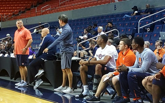 Auburn center Austin Wiley (center) sits on the bench with a boot on his injured left foot.