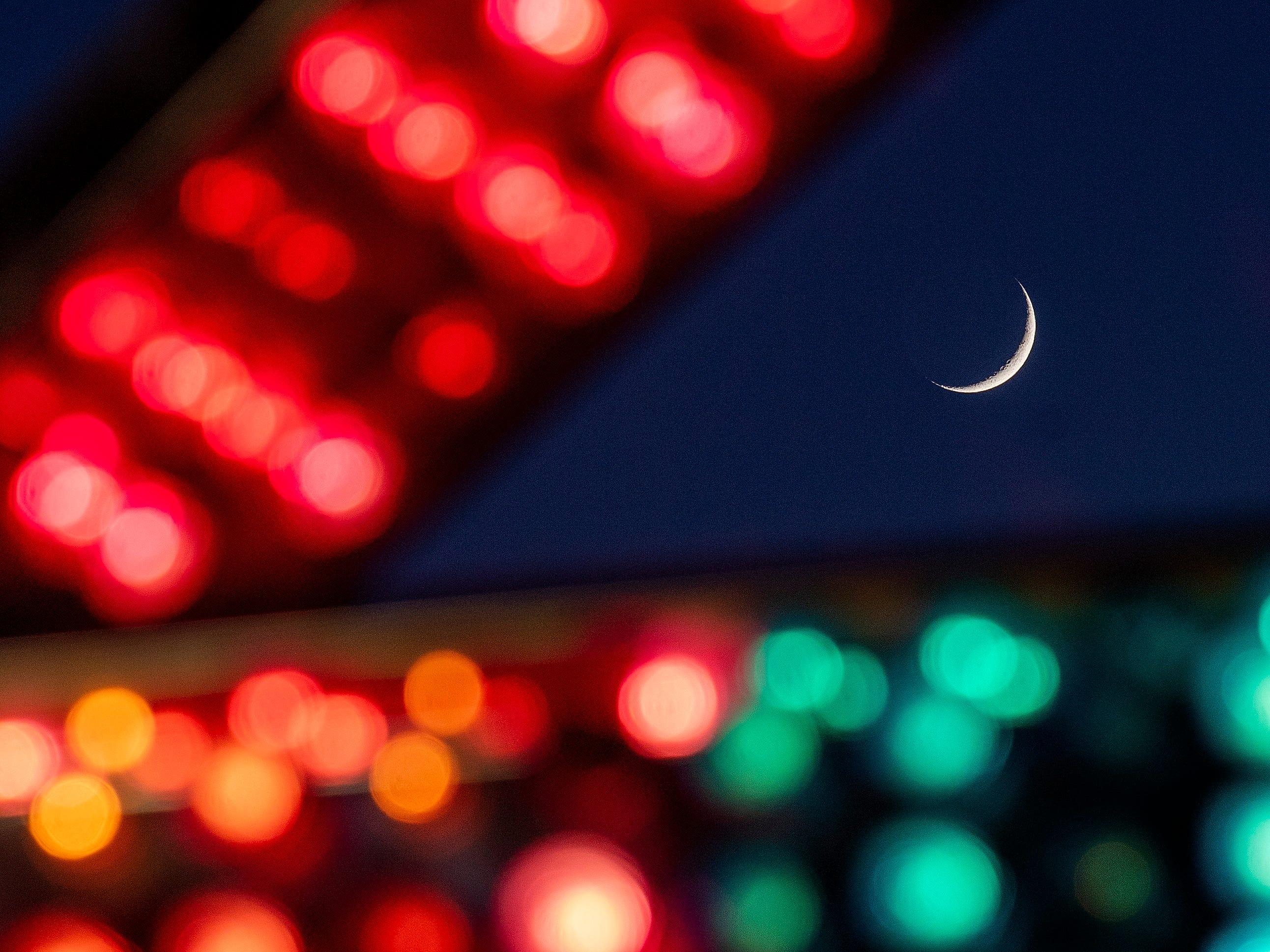 The crescent moon rises as families enjoy the Autauga County Fair in Prattville, Ala., on Thursday evening October 11, 2018. The fair runs through Saturday the 13th.