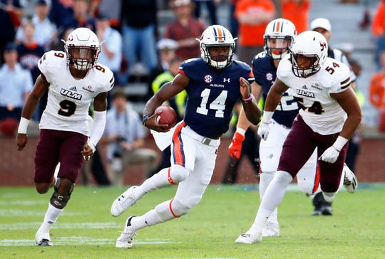 Auburn quarterback Malik Willis (14) gets past UL Monroe defenders during the fourth quarter at Jordan-Hare Stadium on Nov. 28, 2017, in Auburn, Ala.