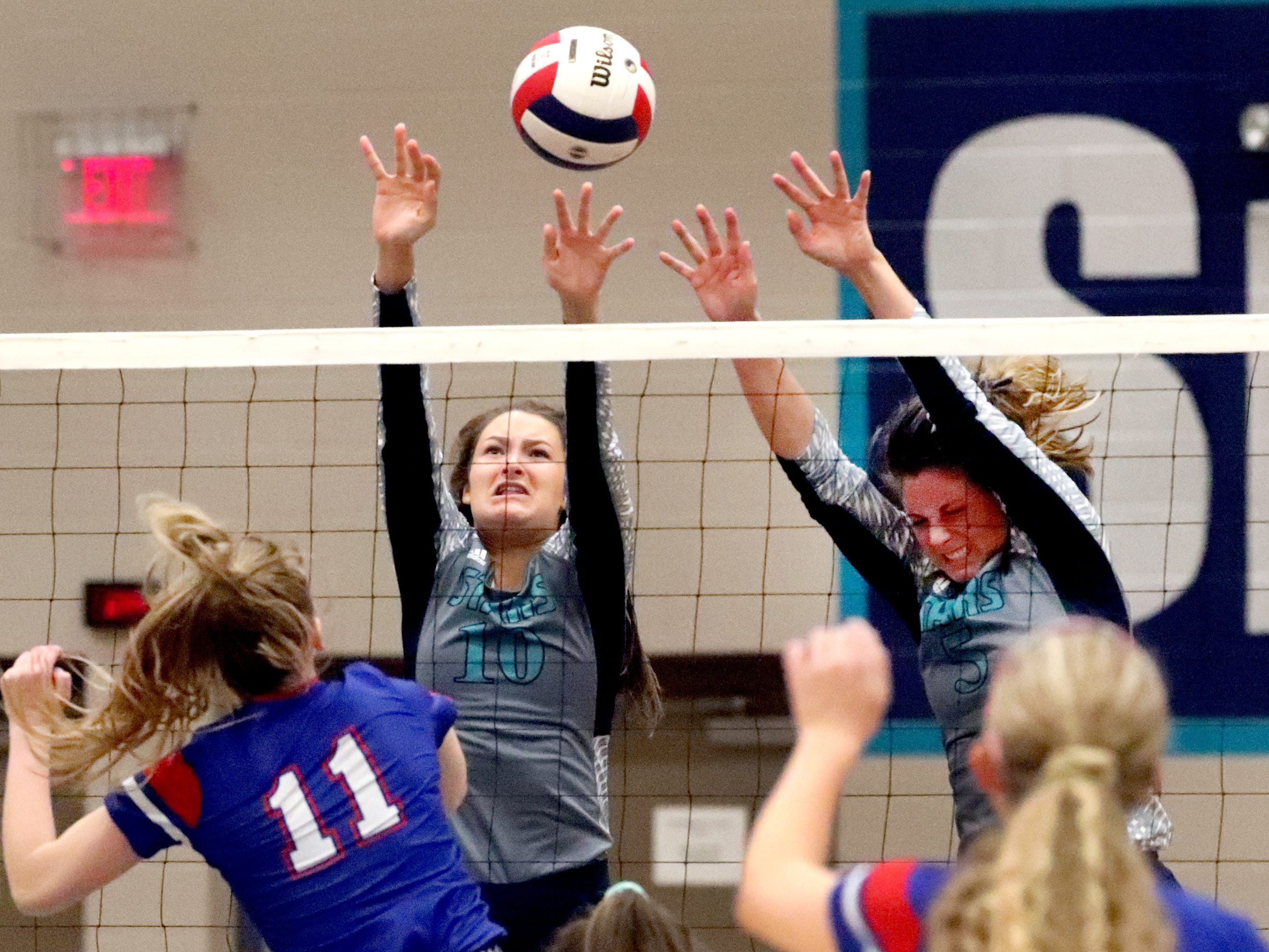 Siegel's Grace Reidmiller (10) and Julia Wheeler (5) defend the net during the Class AAA sectional against Cleveland Thursday, Oct. 11, 2018. Siegel beat Cleveland to advance to the State Championship tournament.