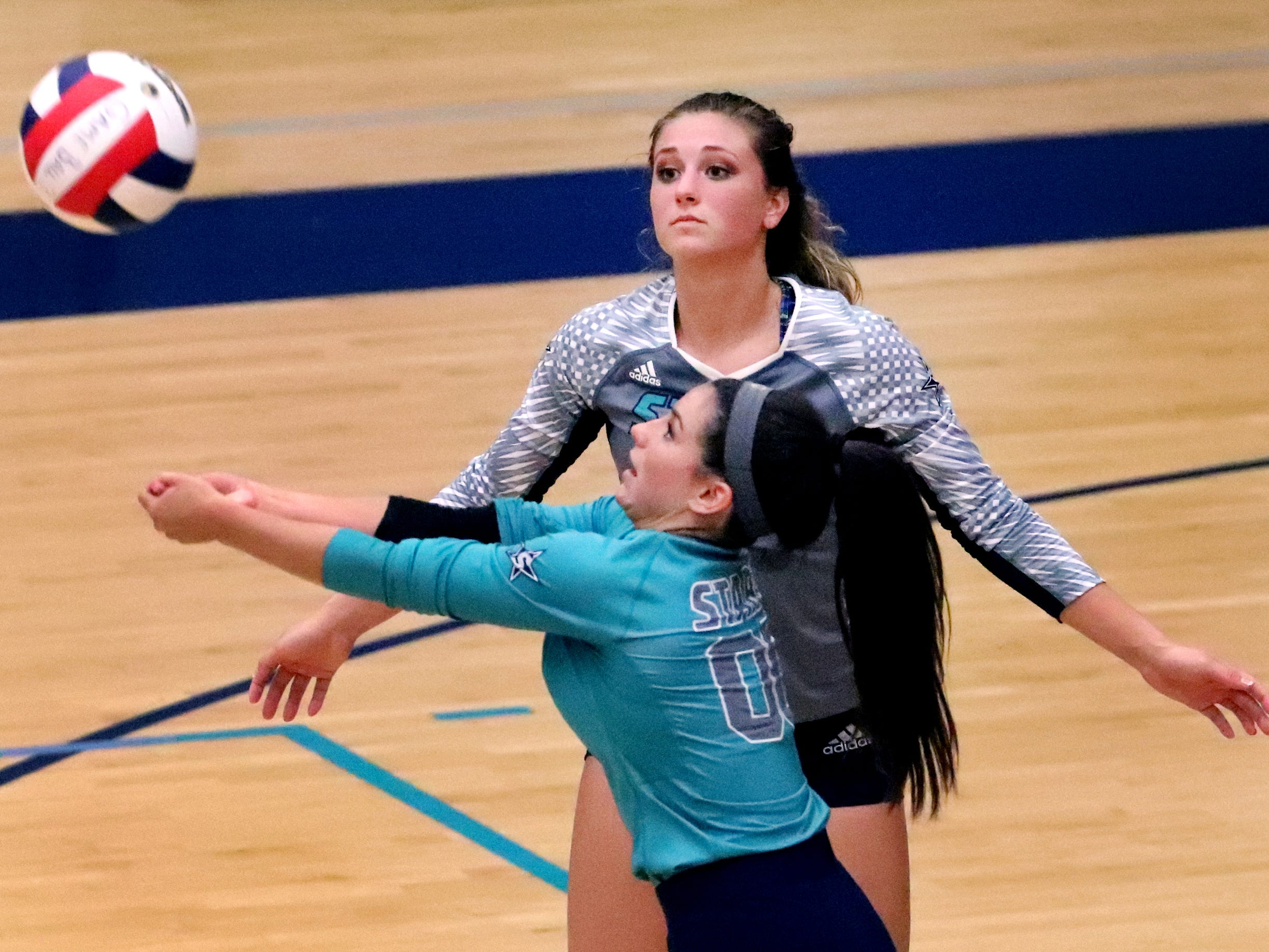 Siegel's Julia Wheeler (5) watches as Julia Poarch (00) bumps the ball up during the Class AAA sectional against Cleveland Thursday, Oct. 11, 2018. Siegel beat Cleveland to advance to the State Championship tournament.