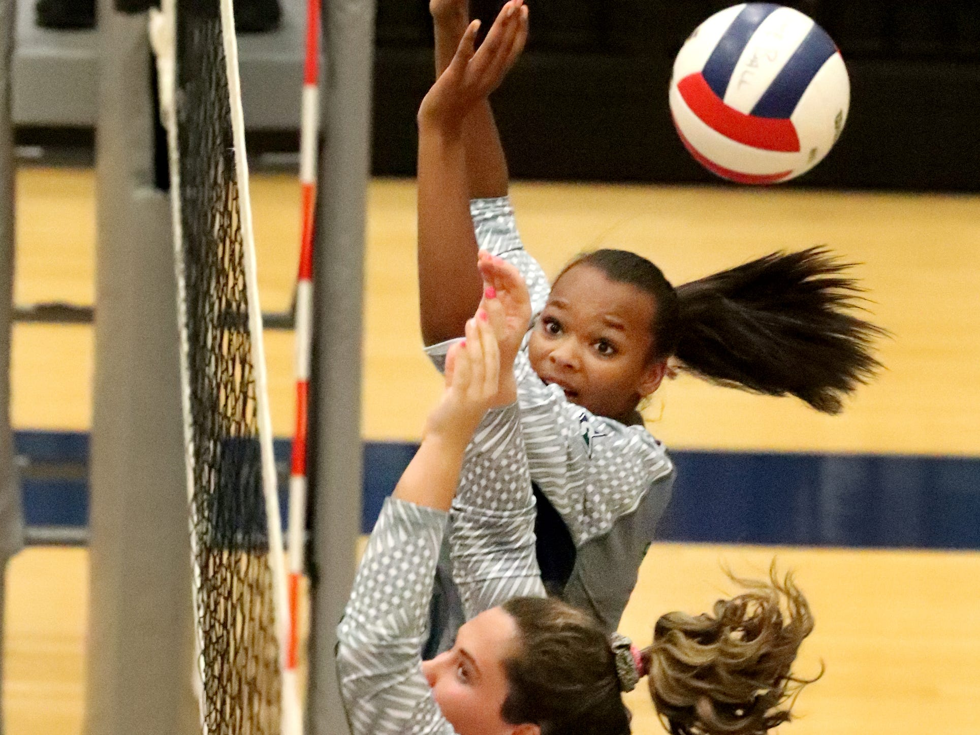 Siegel's Jaida Clark (7) and Sydney Taylor (14) defend the net during the Class AAA sectional against Cleveland Thursday, Oct. 11, 2018. Siegel beat Cleveland to advance to the State Championship tournament.