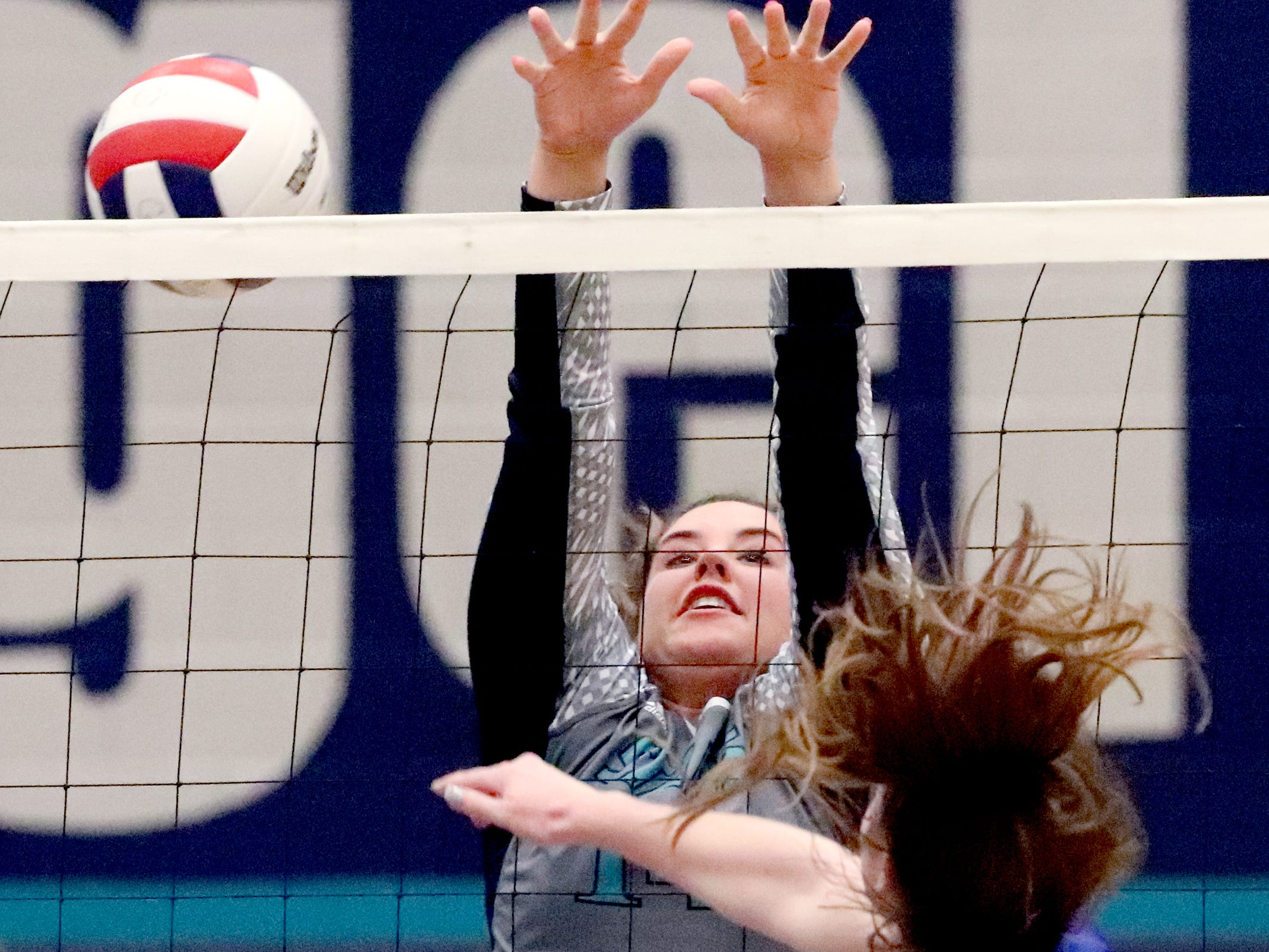 Siegel's Sydney Taylor (14) defends the net as Cleveland's Lily Oliver (17) hits the ball over the net during the Class AAA sectional against Cleveland Thursday, Oct. 11, 2018. Siegel beat Cleveland to advance to the State Championship tournament.
