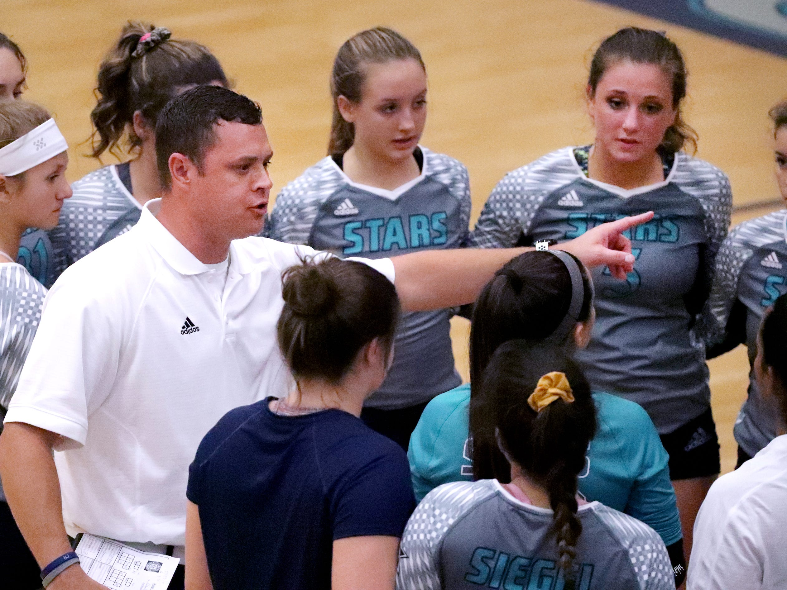Siegel's head volleyball coach Shawn Robinson talks to his team during a break in the game as they take on Cleveland in the Class AAA sectional Thursday, Oct. 11, 2018.