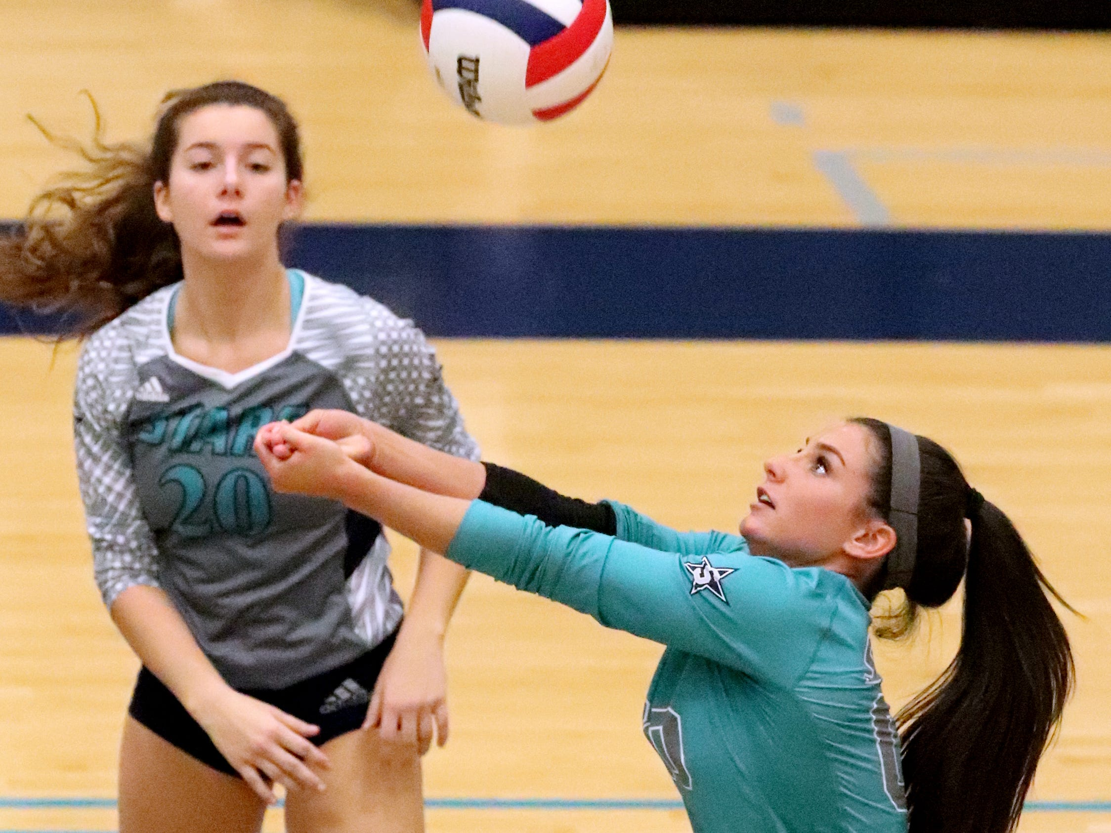 Siegel's Julia Poarch (00) bumps the ball as Zoe Delk (20) watches in the background during the Class AAA sectional against Cleveland Thursday, Oct. 11, 2018. Siegel beat Cleveland to advance to the State Championship tournament.