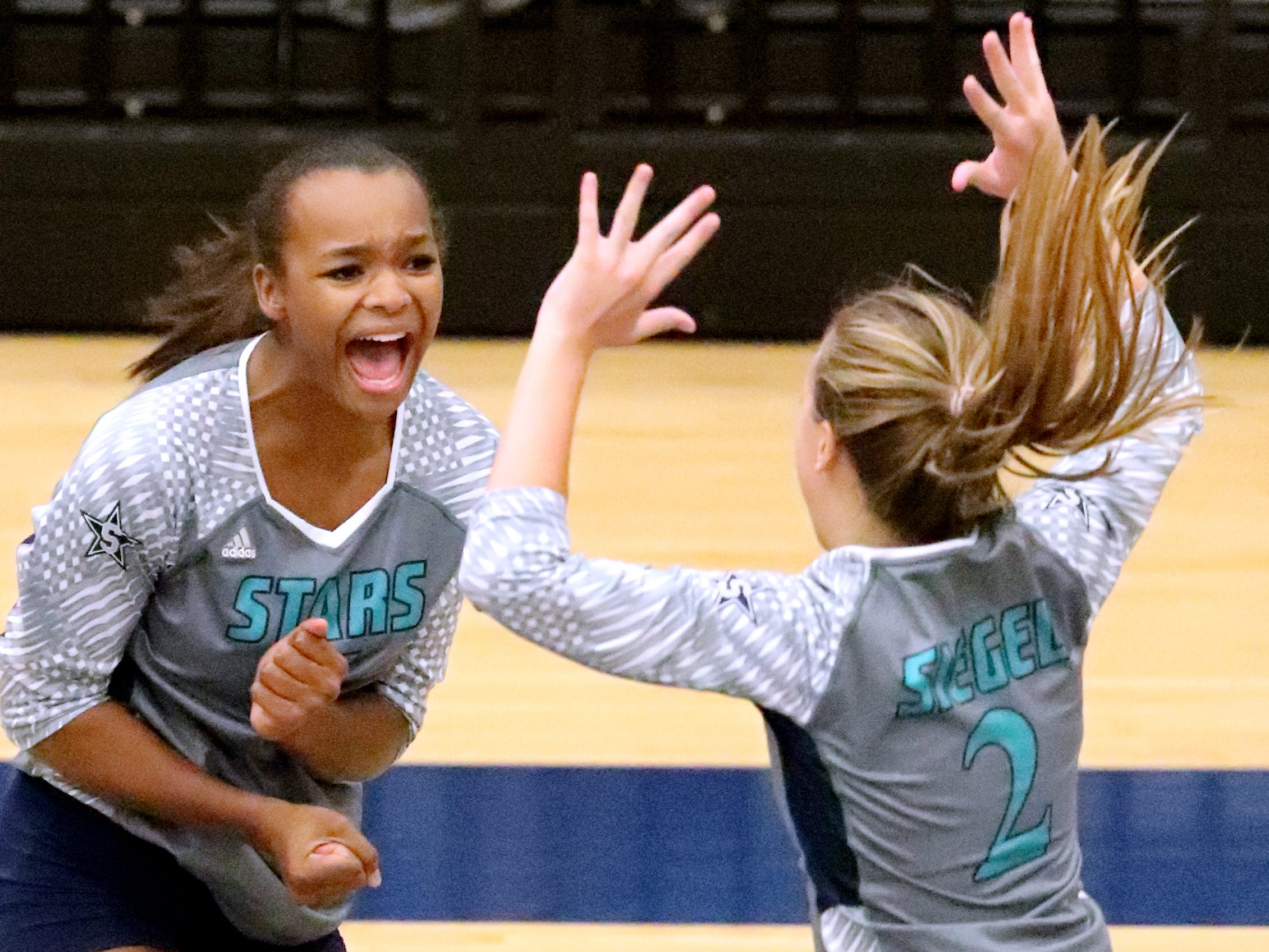 Siegel's Jaida Clark (7) and Emily Wessner (2) celebrate a point over Cleveland in the Class AAA sectional Thursday, Oct. 11, 2018, at Siegel.
