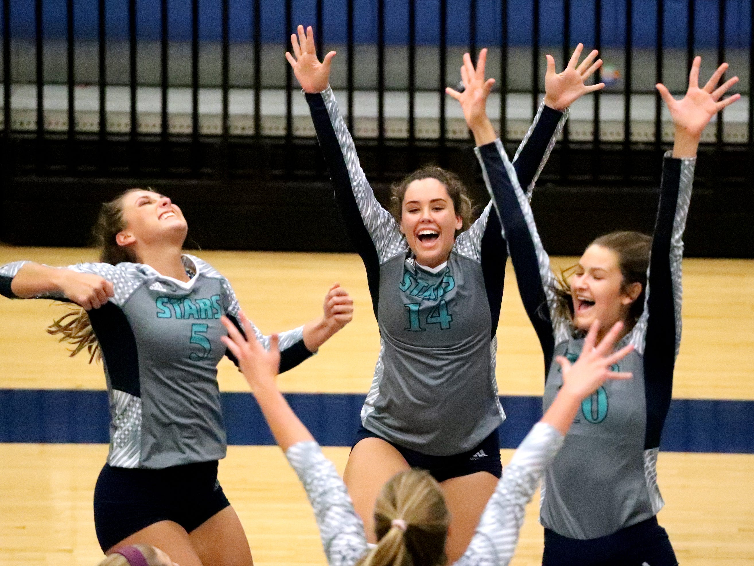 Siegel's Julia Wheeler (5), Sydney Taylor (14) and Grace Reidmiller (10) celebrate wining a point over Cleveland in the Class AAA sectional Thursday, Oct. 11, 2018, at Siegel.