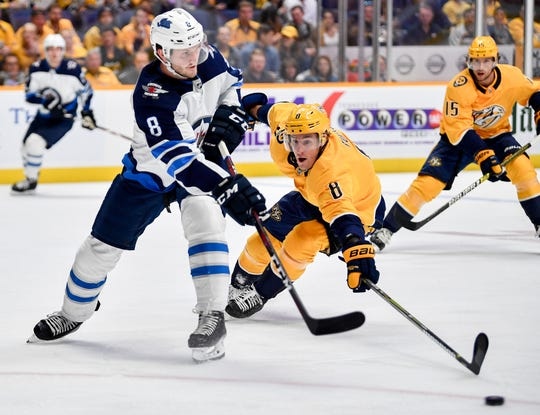 Winnipeg Jets defenseman Jacob Trouba (8) passes past Nashville Predators center Kyle Turris (8) during the first period at Bridgestone Arena in Nashville, Tenn., Thursday, Oct. 11, 2018.