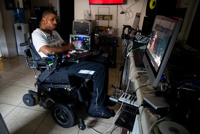 """George Smith plays the music video for 'Pree' by H.I.S., an artist that he works with, on Thursday at his home studio in Immokalee. Smith was injured 20 years ago in a high school football game that left him paralyzed. """"Music has been therapy to me,"""" he said."""