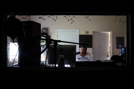 George Smith plays music from his Soundcloud on Thursday at his home studio in Immokalee.