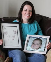 In this 2011 file photo, Beth Adkins holds a picture of her son, Wyatt, who was born with hypoplastic left heart syndrome (HLHS) and died in 2008.
