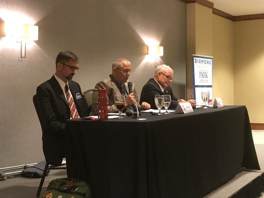 Commissioner Rick Black, right, and challenger Adam Rhodes, left, listen to moderator Dave Doney at the Licking County Chamber debate on Oct. 11, 2018.