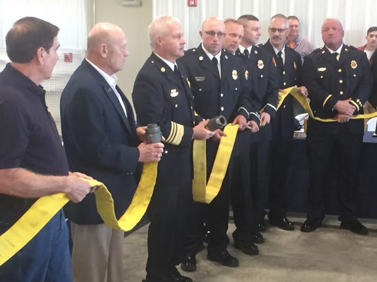 Instead of cutting a ribbon, past and present firefighters disconnected a yellow fire hose to officially open the new station.