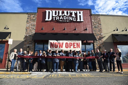 Staff members of Duluth Trading Company take part in a ribbon-cutting ceremony outside the Ramsey store in September 2018.