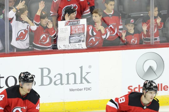 Youngsters try to get the attention of Devils players as they warm up before the game. Thursday, October 11, 2018