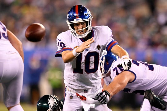New York Giants quarterback Eli Manning (10) throws the ball to the ground as he's sacked by Philadelphia Eagles defensive tackle Fletcher Cox, bottom, in the second half. The New York Giants lose 34-13 to the Philadelphia Eagles on Thursday, Oct. 11, 2018, in East Rutherford.