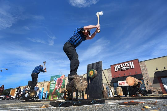 Lumberjacks Nick Hastedt, foreground, and Dave Weatherhead of Timberworks Jackshow.com from Wisconsin compete in the wood chopping contest during the opening day of a Duluth Trading Co. store.