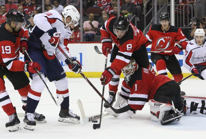 The puck is shown between the sticks of Will Butcher (8) and Keith Kinkaid (1), of the Devils.  Kinkaid and the Devils went on the shutout the Capitals, 6-0.  Thursday, October 11, 2018