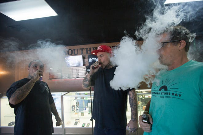 "Marlo Mac Flores, left,  manager of Southwest Vape and Ray Vigil, the store's owner,  and Doug Vernon, demonstrate ""Cloud Chasing"" while vaping. Thursday October 4, 2018."