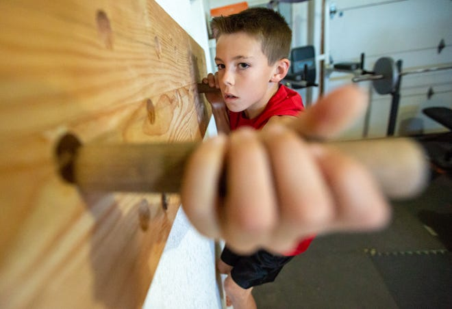 "Miles Odom, 10, of Las Cruces, trains at his home on Wednesday, October 10, 2018. Odom is known as the, ""Barefoot Warrior"" when he is participating as a contestant on America Ninja Warrior Jr. The season premiere is scheduled to air on television Saturday."