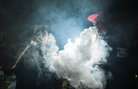 Marlo Mac Flores, left, manager at South West Vape and Ray Vigil, the store's owner, blow large clouds while vaping.