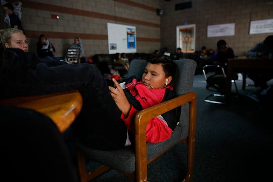 Ismael Carmona, 13, watches YouTube videos on his smartphone at the Boys & Girls Clubs of Farmington on Friday.