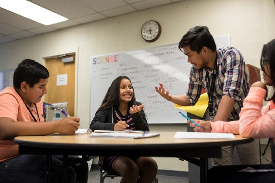 """Kimberly Reveles (center) laughs while John Perales (right) assists her with an in class exercise as Anthony Mendoza looks on during his seventh grade biology class at Hezer Middle School in Hobbs. Perales was recruited to teach in the United States on a J-1 """"cultural exchange"""" visa that is temporary, paid by the teacher and cannot be easily parlayed into permanent residency."""