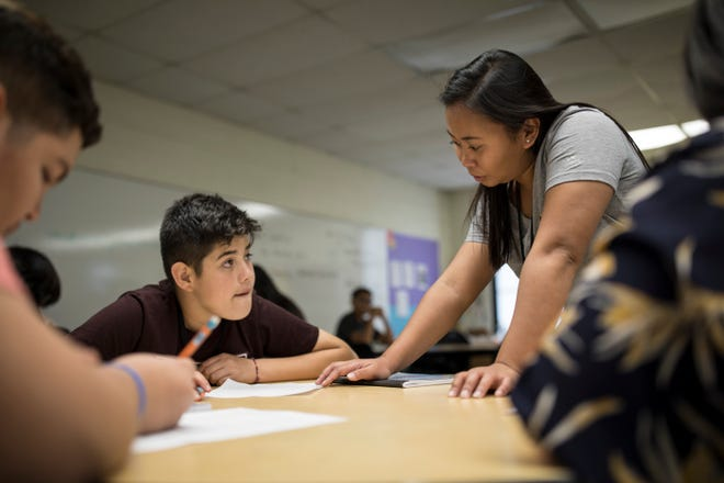 Filipino teacher Cindy Serrano assists Juan Caamano (left) with an in-class exercise during her biology class at Heizer Middle School. Serrano taught for five years in the Philippines and is in her second year of instruction in Hobbs.